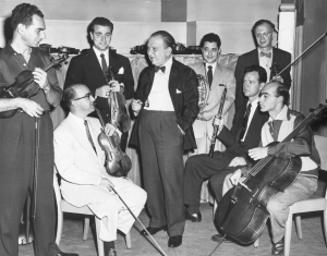 Fritz Reiner and the newest members of the Orchestra in the fall of 1953. From left to right: Nathan Snader, violin; Juan Cuneo, violin; Joseph Golan, violin; Alan Fuchs, horn; Sheppard Lehnhoff, viola; Ray Still, oboe; Sheppard Lehnhoff, viola; and János Starker, cello.