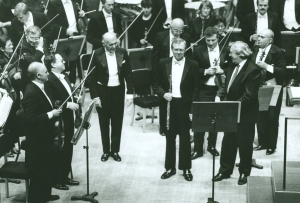 Sir Georg Solti and the composer acknowledge soloist Walfrid Kujala following the world premiere of Schuller's Concerto for Flute and Orchestra on October 13, 1988